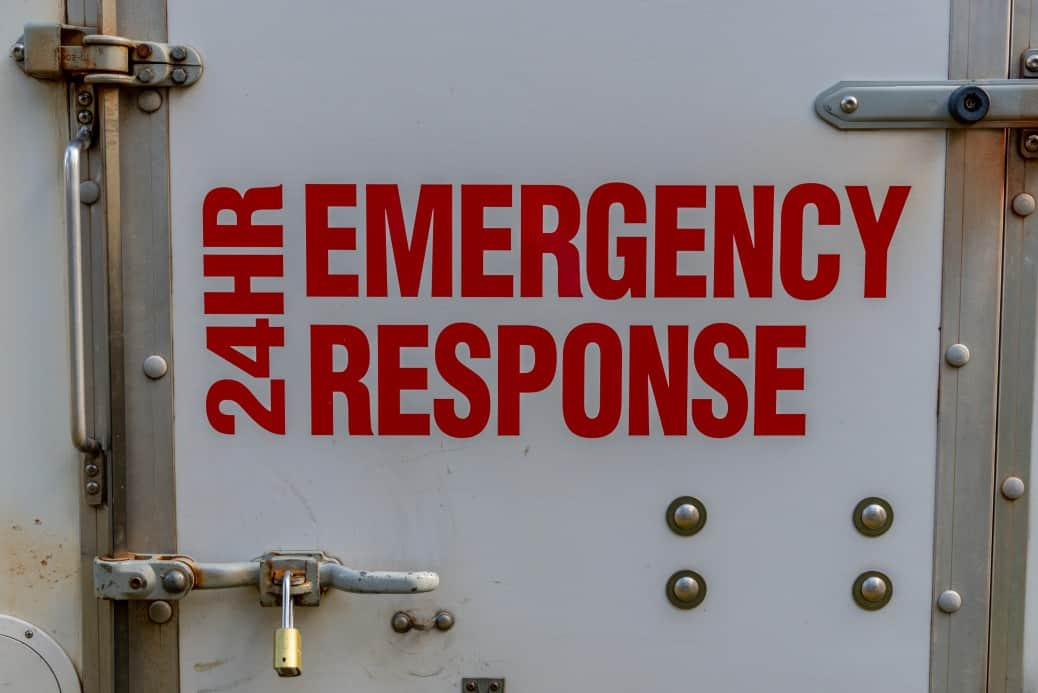 A door that says 24 hour emergency response in red letters