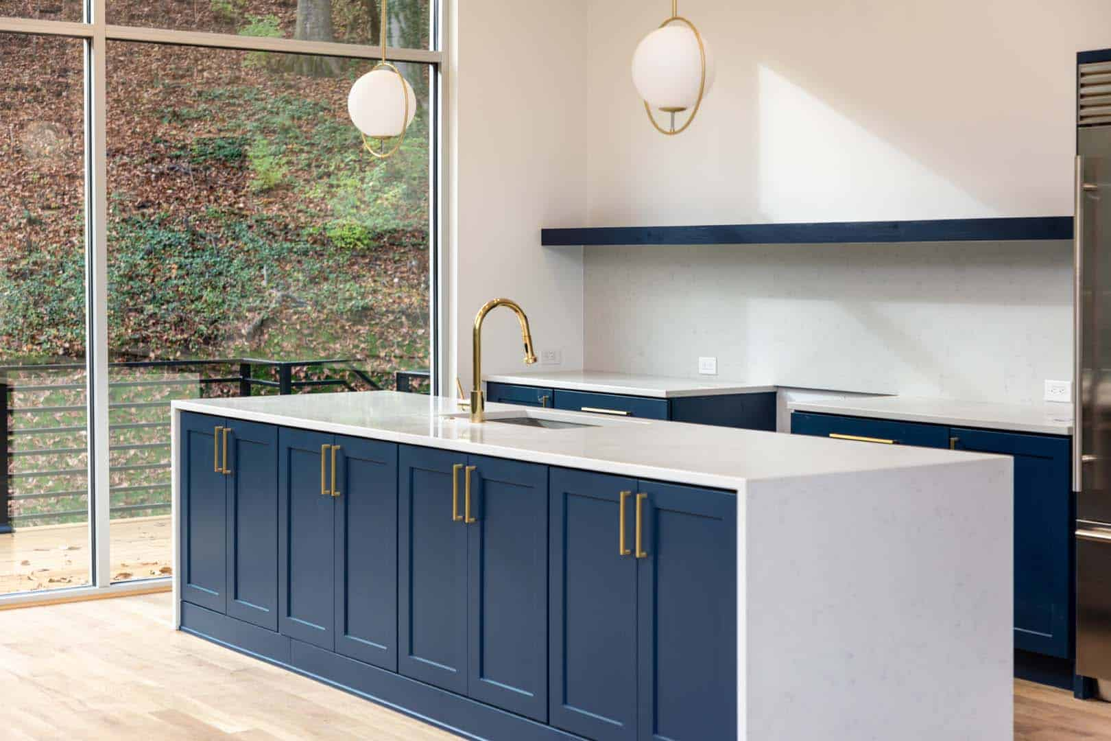 A kitchen island with blue cabinets and a golden sink faucet next to a large window