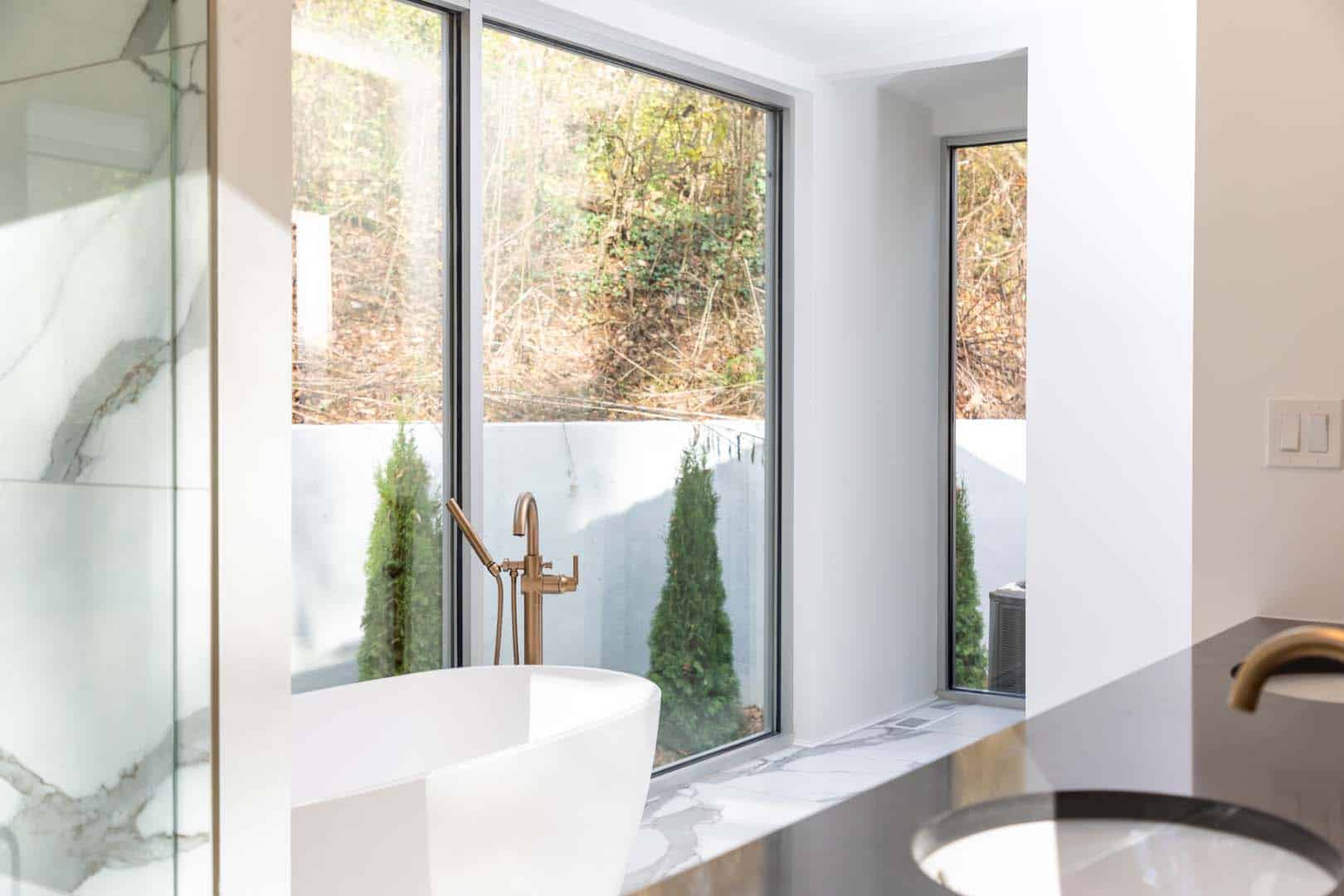 An out of focus golden faucet in the foreground with a white bathtub and large windows in focus