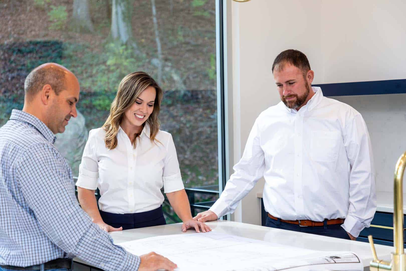 The owners of Bio Plumbing looking at a blueprint with a client