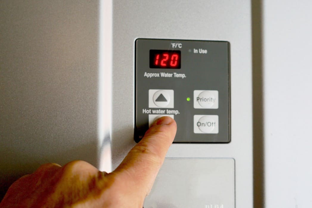 A close up finger changing the temperature on an electric water heater