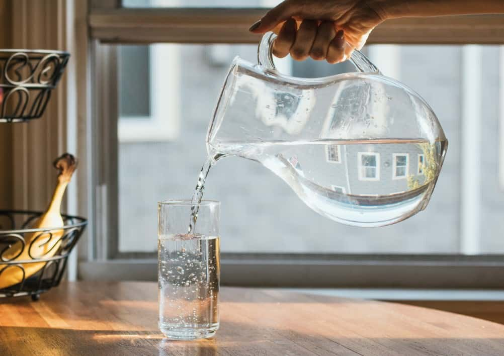 Pouring a glass of water out of a glass pitcher into a clear glass sitting on a wooden countertop with a banana in the background